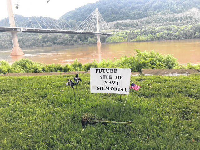 A sign marks the planned future location of the memorial in York Park along the Ohio River.