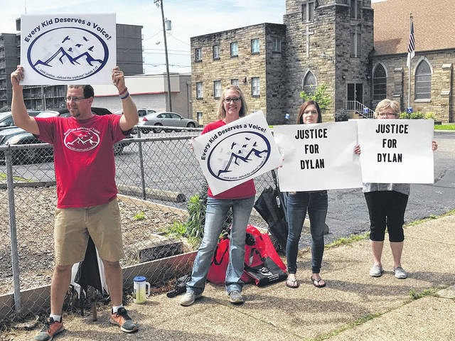 Protesters making their presence known near the parking lot of Scioto County Childrens Services included, from left, Adam and Katie Smith, organizer Stephanie Carter and her mother Carla Teresian.