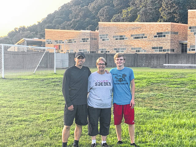 New Boston soccer head coach Greg Mauk (left), Kim Lawless (middle), and senior captain Malachi Potts (right) pose for a picture in New Boston Municipal Stadium, home of the New Boston Tigers soccer program.