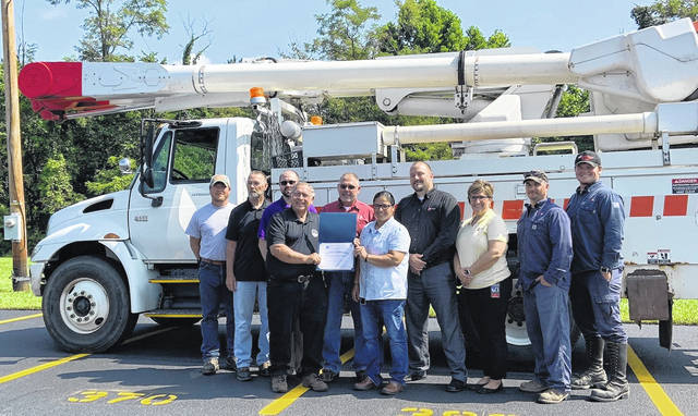 AEP has once again donated a truck to the Scioto County Career and Technical Center for use in teaching students line work as well as CDL training. Back Row: (left to right) Lee Adkins, Roy Bennett, Derek Brown, Brent Koenig, Anthony DeBord, Kelly Bussler, Donald McCormick, Todd Adkins. Front Row: (l to r)Kenny Renn, Michele Ross.