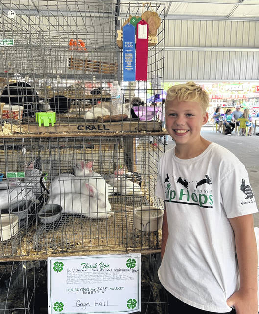 Gage Hall with his Grand Champion Market Rabbit.