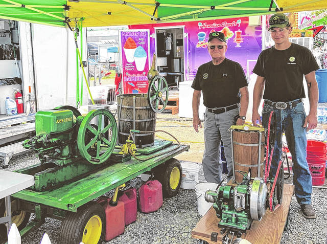 Bob Thomas (left) and Alex Otworth making homemade ice cream at the fair. The old motor is on the left with the John Deer small wagon and the new one that Otworth bought is in front of them churning out the ice cream.