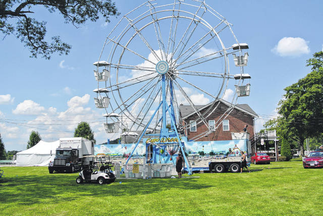 Workers assemble the ferris wheel in preparation for the Scioto County Fair.