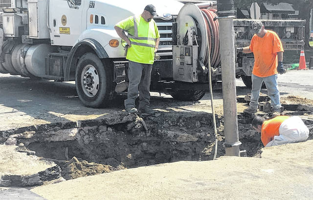 City workers Monday work to repair a void beneath Coles Boulevard.