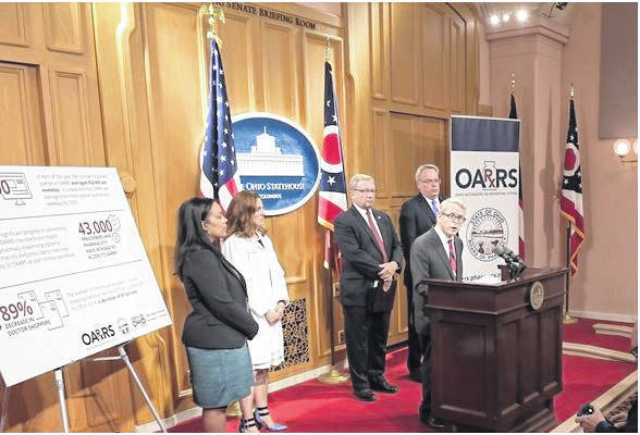 With U.S. Drug Czar Jim Carroll, left, and state pharmacy board Director Steven Schierholt behind him, Gov. Mike DeWine talks about record use of the Ohio Automated Rx Reporting System.