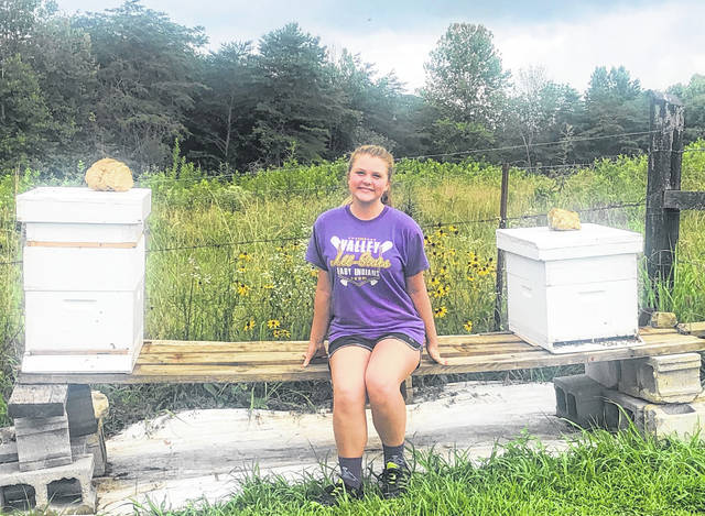 Abby Webb with her beehives that she created as part of her project to receive the Silver Award in Girl Scouts.