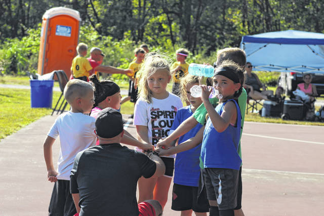 Players in the McGraw Fall Basketball League gather around their coach Sunday at the McGraw Basketball League courts at 1321 State Route 140, Portsmouth.