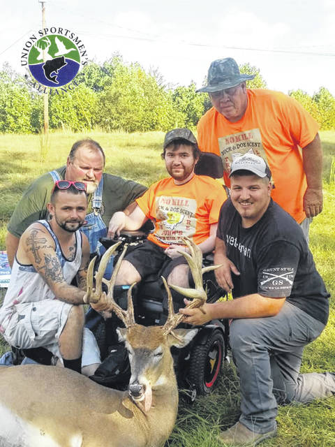Justin Hatton, middle, with his trophy buck he brought down at his No Kill deer hunt Saturday. Hatton is surrounded by family and friends.