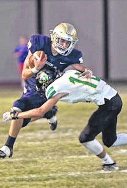 Notre Dame's Logan Emnett with a carry while being tackled by Greenup County's Brayden Craycraft Friday night at Spartan Stadium.