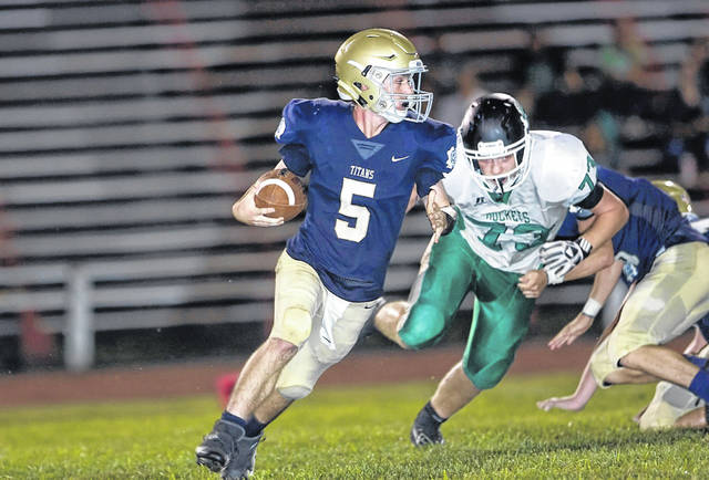 Notre Dame junior quarterback Jake McGuire scrambles for yardage in the Titans home loss to Fayetteville-Perry Friday.