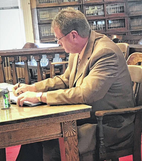Indicted Pike County Sheriff Charles Reader spent the time leading up to a Thursday pretrial writing in a notebook.