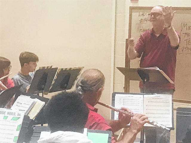 Director Terry Thompson puts the members of the symphony through their paces during a recent rehearsal.