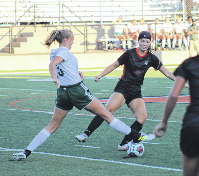 Wheelersburg's Brittani (8) Wolfenbarker battles Athens' Karma Fugate (23) for possession of the ball during Tuesday's Division II girls soccer sectional semifinal match at Wheelersburg High School's Ed Miller Stadium.