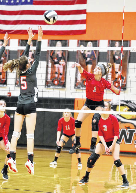 Minford's Ezra Veach (1) goes up for a kill over Westfall's Peyton Proffitt (5) during Wednesday's Division III district semifinal volleyball match at Waverly High School.