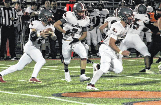 Minford quarterback Elijah Vogelsong-Lewis (2) keeps the ball as he fakes to teammate Matthew Risner (7) during the Falcons' Southern Ohio Conference Division II football game against Waverly on Friday night at Waverly's Raidiger Field.