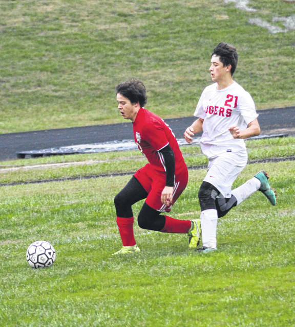 Minford senior Brayden Davis is tracked down in the corner by New Boston's Levi Bowman (21) during Wednesday's Division III boys soccer sectional championship match at Minford High School.