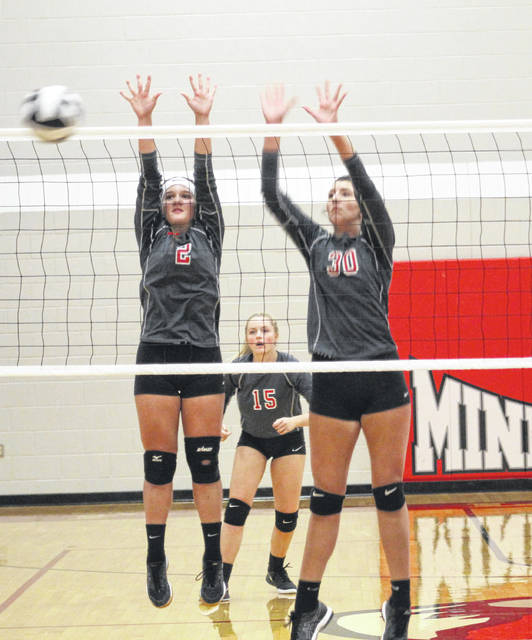 Minford's Nicole Collier (2) and Ally Coriell (30) combined for this block during the Lady Falcons' Division III sectional championship volleyball match against Chesapeake on Saturday at Minford High School.