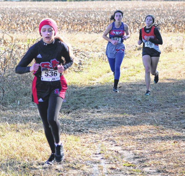 South Webster's Macie Rhoads (front), Northwest's Brooke Shope (back left) and Wheelersburg's Amanda Salmons (back right) compete in the girls high school race as part of Saturday's Southern Ohio Conference championship cross country meet at Waverly's Bristol Park.