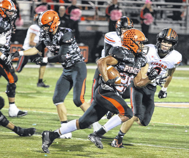Wheelersburg's Makya Matthews (29) tries to run past Waverly's Penn Morrison (9) during Friday night's Southern Ohio Conference Division II football game at Wheelersburg High School's Ed Miller Stadium.