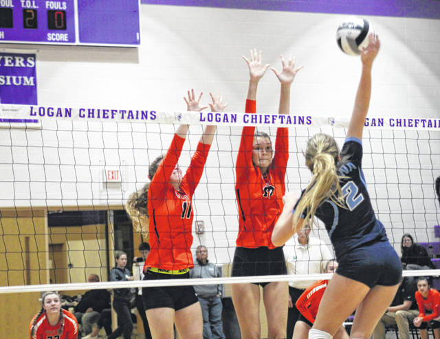 Wheelersburg's Kylee Barney (12) and Lauren Jolly (11) go up for a block against Adena's Hannah Burns (2) during Thursday night's Division III regional semifinal volleyball match at Logan High School's Jim Myers Gymnasium.