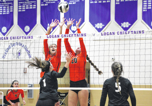 Wheelersburg's Kylee Barney (12) and Mallory Bergan (20) go up for a block over Hiland's Madison Yoder (1) during Saturday's Division III volleyball regional championship match at Logan High School's Jim Myers Gymnasium.