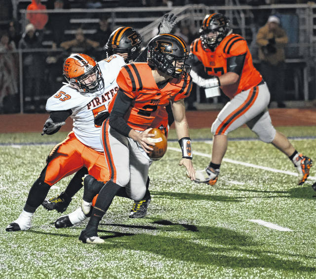 Wheelersburg senior Brady Warner (53) pursues Ridgewood quarterback Gabe Tingle (2) during Saturday night's Division V Region 19 semifinal football playoff game at Lancaster's Fulton Field.