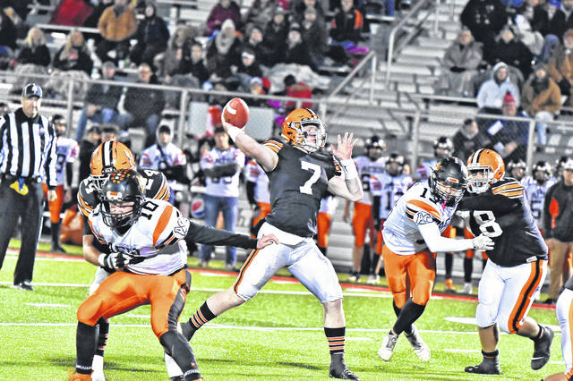 Ironton quarterback Gage Salyers (7) throws the football as teammates Ryan Cecil (78) and Ashton Duncan (24) block during the Fighting Tigers' Division V Region 19 semifinal football playoff game against Amanda-Clearcreek.