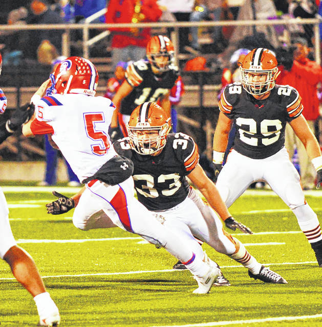Portsmouth quarterback Drew Roe (5) tries to escape the tackle of Ironton's Dalton Crabtree (33) during Friday night's Ohio Valley Conference football game at Ironton's Tanks Memorial Stadium.