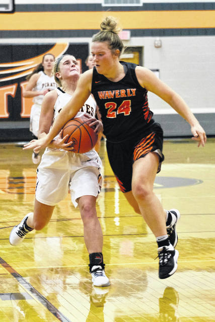 Wheelersburg's Madison Whittaker (12) is bumped by Waverly's Zoiee Smith (24) during Thursday night's Southern Ohio Conference Division II girls basketball game at Wheelersburg High School.