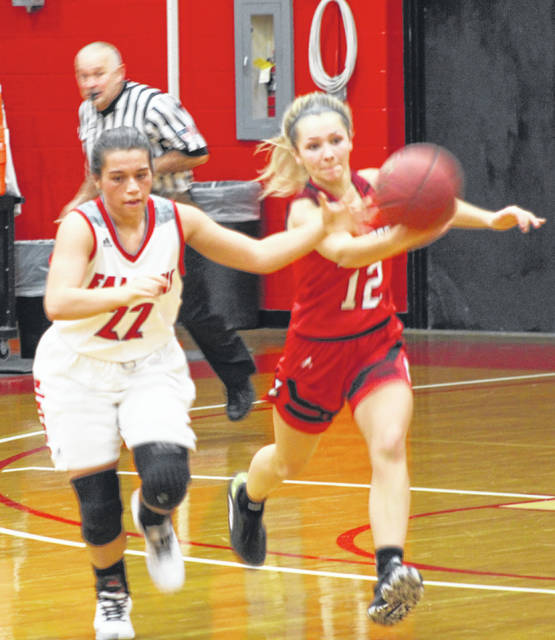 Minford senior Maddie Slusher (22) tries to keep possession of the ball from Eastern Brown's Rylee Leonard (12) during Saturday's non-league girls basketball game as part of the Woods Lumber Classic at the University of Rio Grande.