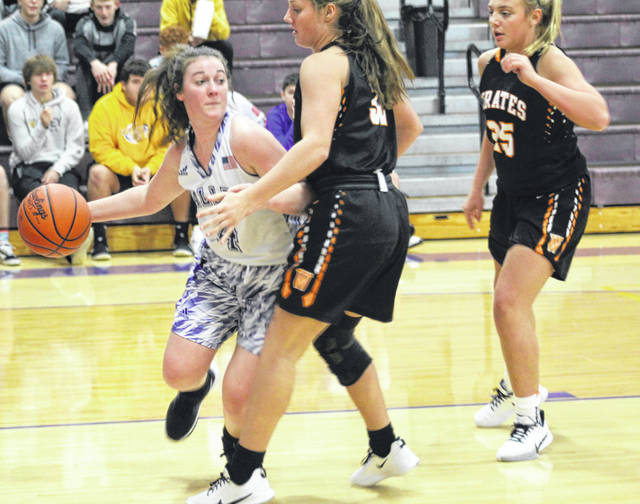 Valley's Brooklyn Buckle (4) makes a pass around the defense of Wheelersburg defenders Macee Eaton (32) and Makenna Walker (25) during Monday night's Southern Ohio Conference Division II girls basketball game at Valley High School.