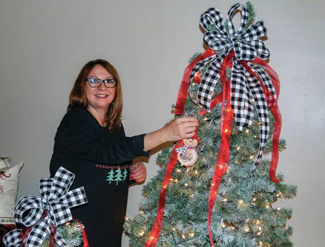 Janie Haas places an ornament on a Christmas tree in your new location.