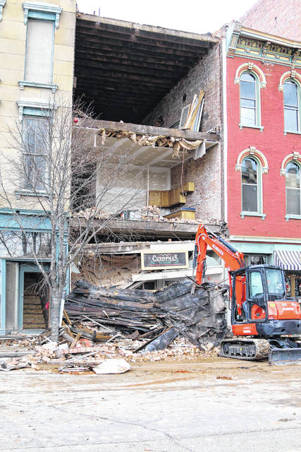 Cleanup crews begin removing debris from the faced of a building in downtown Portsmouth Sunday afternoon.