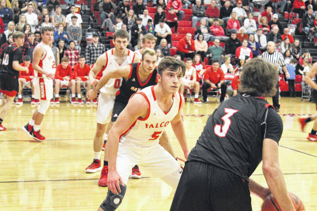 Minford junior Skyler Knore (5) defends Oak Hill's Keaton Potter (3) while fellow Falcon Hunter Davis (0) defends Oak Hill's Chase Hammond (24) on the low-block in Minford's 55-49 home loss to the Oaks on Tuesday.