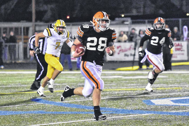 Ironton's Reid Carrico (28) rushes for a 70-yard touchdown during the Fighting Tigers' Division V state semifinal football playoff game against West Jefferson. Trailing the play for the Fighting Tigers is Asthon Duncan (24).