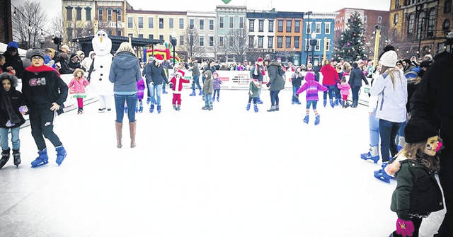 A photo taken during last year's Winterfest at the ice skating rink with the decorated town in the background.
