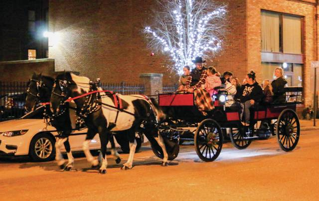Families travel down Second Street in a horse-drawn carriage during Winterfest.