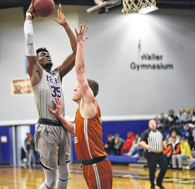 Shawnee State's E.J. Onu (35) goes up for a shot over Lourdes' Nick Welch during Monday night's non-conference men's college basketball game at the James A. Rhodes Athletic Center.