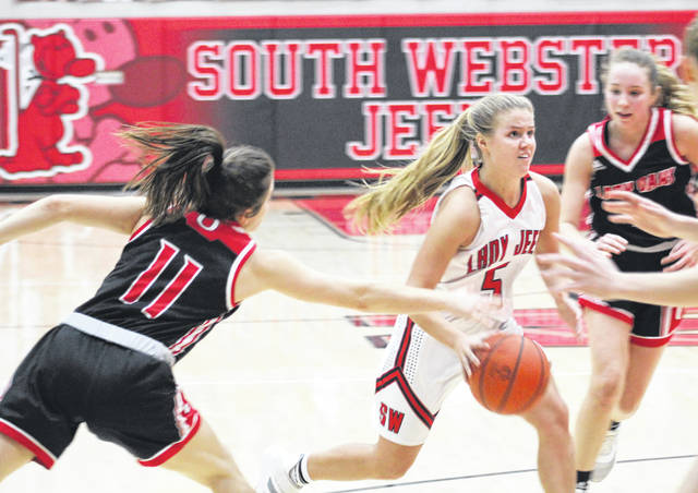 South Webster's Kenzie Hornikel (5) drives to the basket as Oak Hill's Caitlyn Brisker (11) reaches in for the ball during Thursday night's Southern Ohio Conference Division II girls basketball game at South Webster High School.