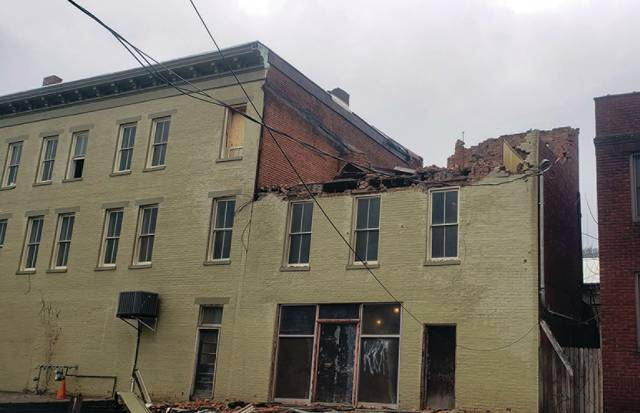 A building near Market Square loses its top story and roof during strong winds Saturday.