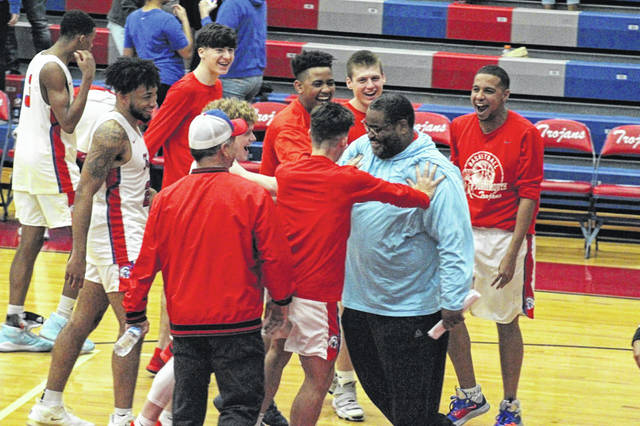 Portsmouth players celebreate with Collins following the Trojans' 72-61 win over Coal Grove in Ohio Valley Conference play. Collins, with the Trojans' 11-point victory, became the second all-time winningest coach in the history of Portsmouth High School boys basketball.