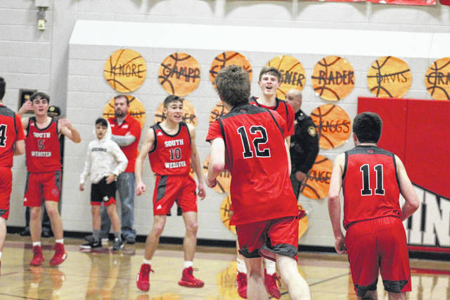 South Webster senior Brayden Bockway (12) rushes off the court with his teammates after scoring a game-high 27 points - including the go-ahead shot with just over seven seconds left - in the Jeeps' 46-43 win over Minford in Southern Ohio Conference Division II play.