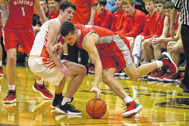 Minford's Elijah Vogelsong-Lewis (3) battles Wheelersburg's J.J. Truitt for possession of a loose ball during Friday night's Southern Ohio Conference Division II boys basketball game at Wheelersburg High School.