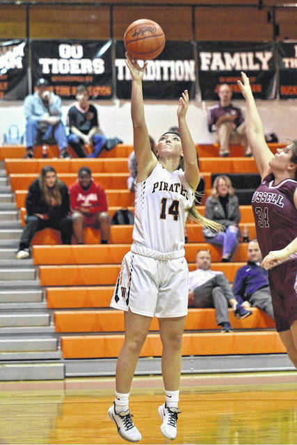 Wheelersburg senior Brittani Wolfenbarker (14) goes up for a basket against Russell's Campbell Jachimczuk (34) during Saturday's girls basketball game as part of the annual Tackett's Body Shop Shootout at Ironton High School.