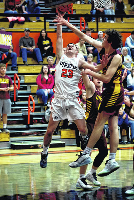 Wheelersburg's Gage Adkins (23) goes up for a shot as Meigs senior Bobby Musser attempts the block during Saturday night's Division III boys basketball sectional championship game at Waverly's Downtown Arena.