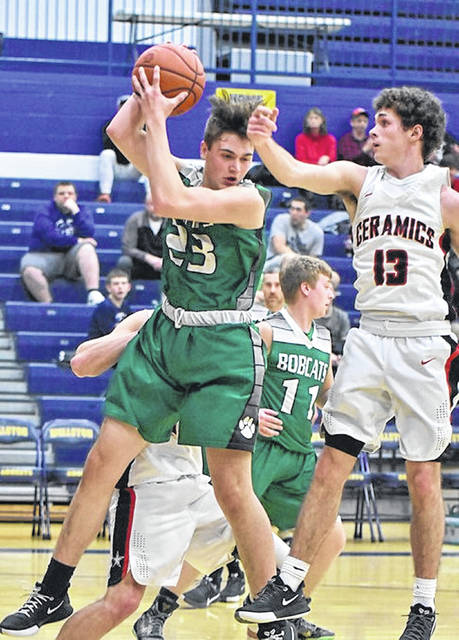Green freshman Levi Sampson (23) grabs a rebound over Crooksville's Tyler Rambo (13) during Tuesday night's Division IV boys basketball sectional championship game at Wellston High School.