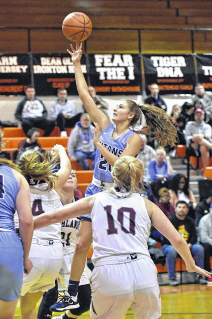 Notre Dame's Isabel Cassidy (20) goes up for a shot over Ashland's Morgan Bradley (4) and Syd Sorrell (10) during Saturday's girls basketball game as part of the annual Tackett's Body Shop Shootout at Ironton High School.