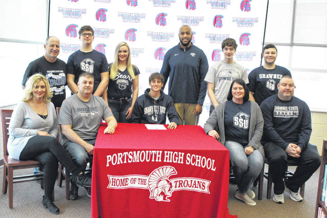 Portsmouth senior Bryce Wallace (center seated) became the latest Trojan to continue his education and swim career under coach Gerald Cadogan at Shawnee State University.