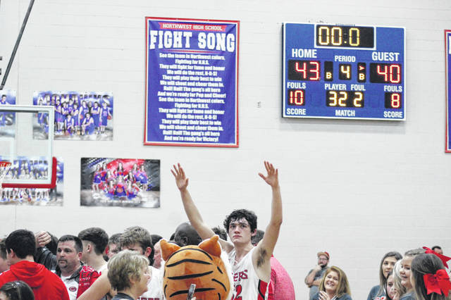 New Boston junior Chase Clark (32) lifts his hands in celebration following New Boston's 43-40 win over Whiteoak in a Division IV sectional final at Northwest High School.