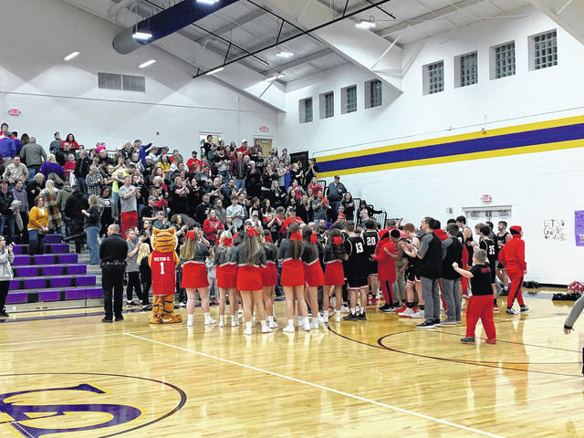 The New Boston boys basketball team and their fans celebrate their first Southern Ohio Conference Divsion I outright championship since 1971 following their 63-60 road win over the Ironton St. Joe Flyers.